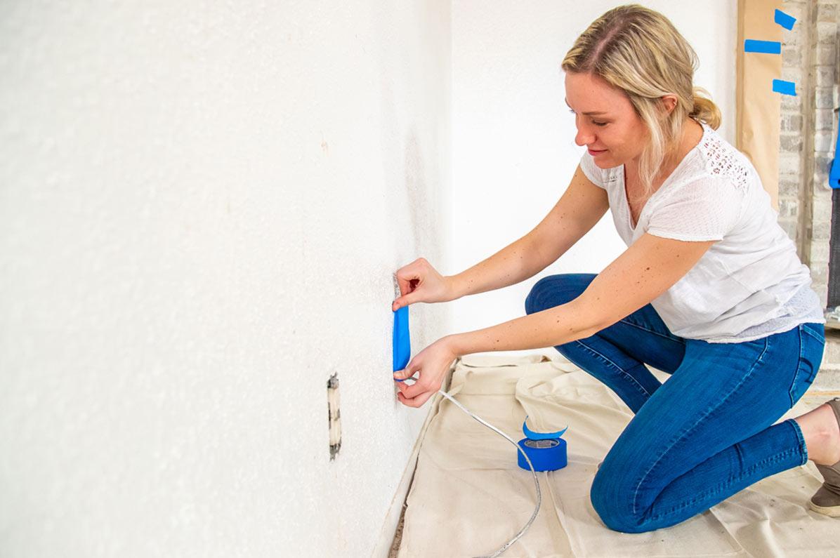 mujer colocando cinta de enmascarar antes de pintar
